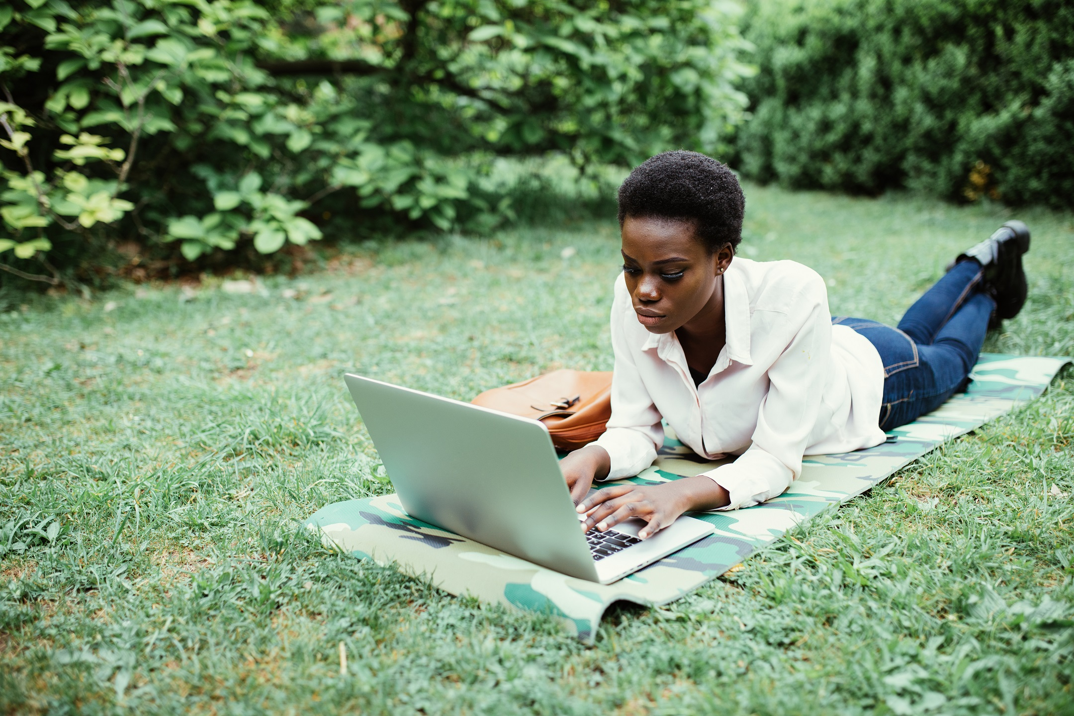 Afro american college student lying down on the grass working on laptop at campus. University.